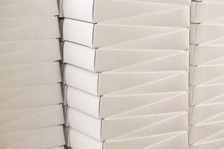 size distribution: Stacks of plain white boxes. Simple white paper boxes. Warehouse of a big company. Cheap delivery for regular customer.