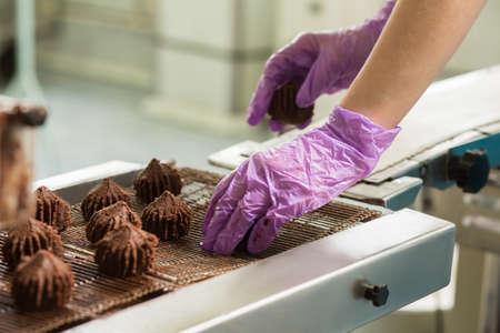 chocolatería: Dé poner dulces en el transportador. Transportador con caramelos de color marrón oscuro. postre popular de chocolate. Densa y deliciosa.
