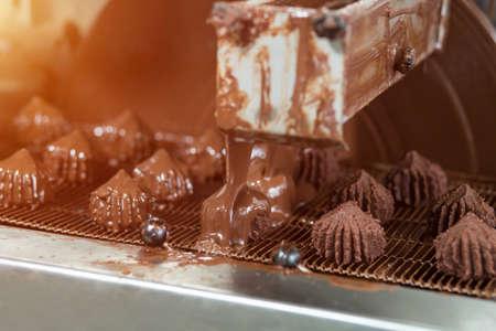 chocolatería: Máquina que vierte el líquido en caramelos. Cinta transportadora con dulces marrones. Producción de postre de alta calidad. Bajo un flujo de chocolate. Foto de archivo