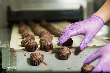 Reihen von Süßigkeiten auf dem Förderer. Hände in den Handschuhen berühren Süßigkeiten. Letzte Produktionsphase. New Dessert im Werk hergestellt.