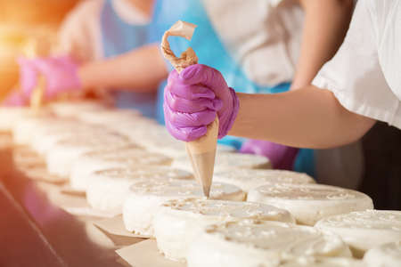 Hand in glove decorating cake. White cakes on production line. Work starts early. Profession that requires skill.
