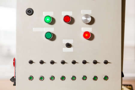 coordinating: Buttons and switches on panel. Gray panel with colorful buttons. Conveyors control panel. Device for coordinating machinerys work.