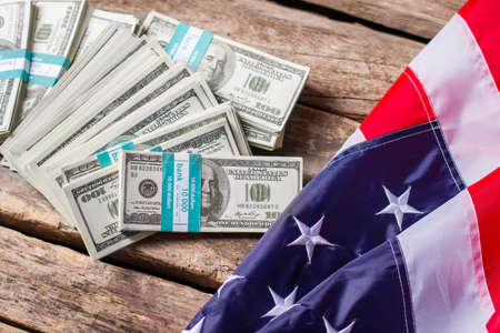 bundles: US flag and dollar bundles. Flag laying near cash bundles. Fruits of diplomacy. Freedom and wealth. Stock Photo