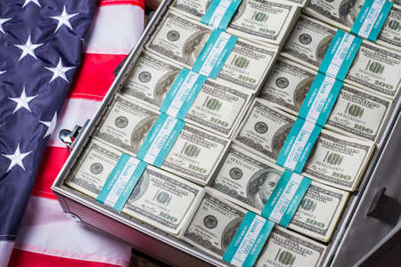Opened case with dollar bundles. US flag, suitcase and money. Bank is growing. The risk is worth it. Imagens