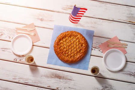 american dessert: American flag, pie and drinks. Table flag beside round pie. Savoury breakfast in american cafe. Simple dessert served with coffee. Stock Photo