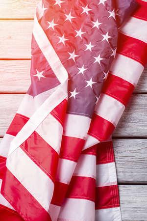 cherish: Creased USA flag under sunlight. Crumpled national flag of USA. Cherish every day of life. Democracy will lead the way.