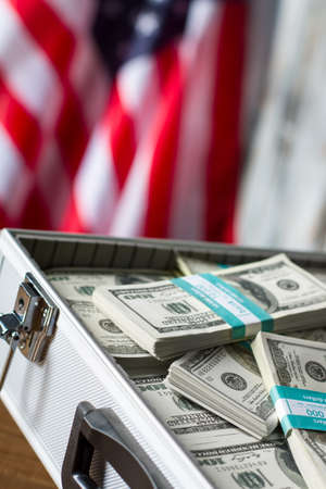 richness: Opened case with dollar bundles. Cash near american flag. Freedom and opportunities. Richness and glory. Stock Photo