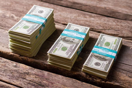 earned: Dollar bundles on wooden background. Cash stacks of different size. Earned with hard labor. Money savings on old table.