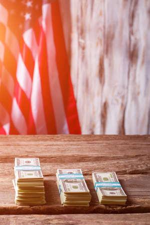 multiplicar: La bandera americana y del dólar haces. Fajos de dinero en efectivo al lado de la bandera. El capital es cada vez mayor. Gane y multiplicarse.