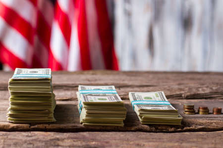 richer: American flag, money and coins. Cash and coins near banner. Progress over the years. Citizens became richer. Stock Photo