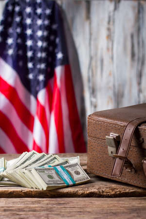 senators: American flag, case and dollars. Brown suitcase near cash bundles. Success and patriotism. Senators monthly salary.