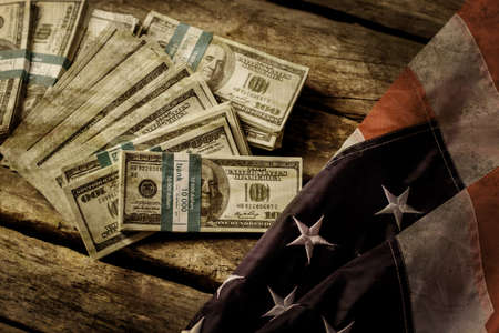 richer: Old USA flag and dollars. Cash laying beside aged flag. Good old times. Nation used to be richer.