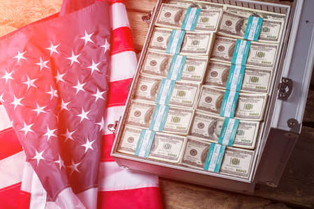 look inside: Case with dollars beside flag. American flag, suitcase and money. Take a look inside. Country gives you good chances.