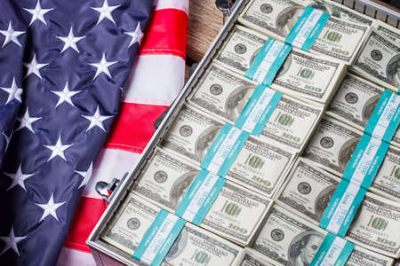strive for: USA flag near dollar bundles. Opened silver case with cash. Pride, wealth and glory. Strive for better. Stock Photo