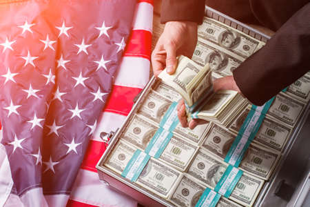 deeds: Hands holding cash near suitcase. USA flag, hands and money. Every decision brings results. Less words more deeds. Stock Photo