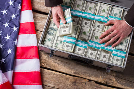 Hand touches dollars in suitcase. US flag laying beside cash. Better hide it away. Greed and fear. Zdjęcie Seryjne