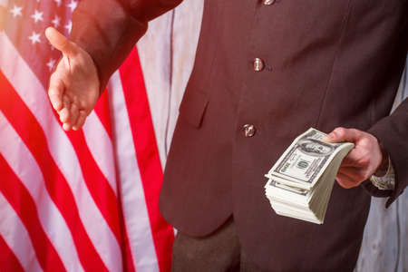 an ally: American flag, businessman and cash. Man with money gives hand. We value every ally. Start of mayors working day.