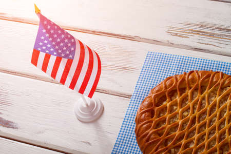 beside table: USA flag, pie and napkin. Pie laying beside table flag. Breakfast of true patriot. Traditional sweet pie with apples.