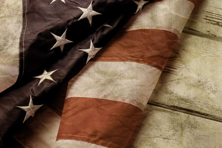long way: Old and crumpled american flag. Aged flag on wooden background. Weve come a long way. Country with strong traditions.