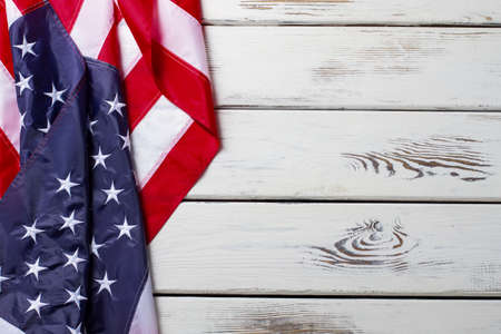 Crumpled American flag. American flag on wooden background. Banner laying on white table. Democracy and freedom.