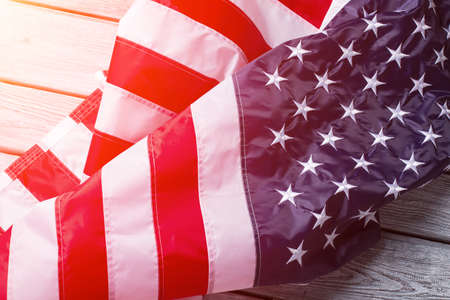 chances: Creased American flag in sunlight. Crumpled banner on wooden background. Every day gives new chances. Never give up.