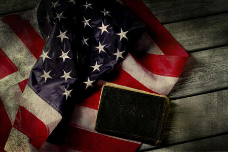 Aged USA flag and book. Book laying beside national flag. Law will protect you. In God we trust. Stock Photo