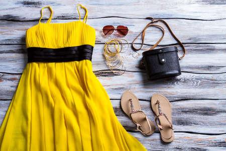 Gele jurk en beige sandalen. Sandalen, kleding en zwarte tas. Stijlvolle jurk met klassieke handtas. Lady's outfit met donkere accessoire.