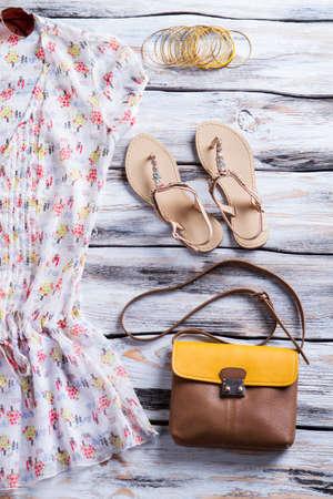 Bluse und Geldbeutel mit Sandalen. Weiße Spitze mit bunten Muster. Mädchen-Casual-Outfit auf dem Display. Leichte Baumwoll und hochwertigem Leder.