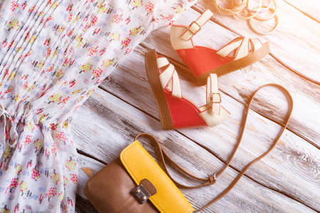 woman's clothing: Wedge sandals and bicolor purse. Colorful bracelet set with bag. Womans summer footwear on display. Clothing and accessories.
