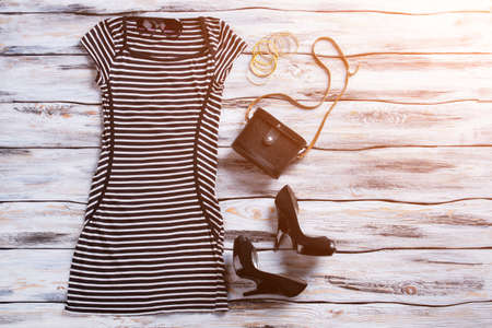 black heels: Striped dress with short sleeves. Black heels and striped dress. Clothes showcase under sunlight. New arrivals in local boutique.