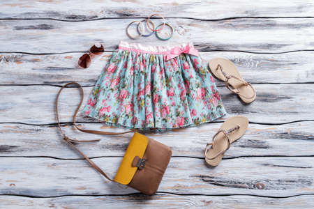 Floral skirt and aviator sunglasses. Bicolor purse with beige sandals. Female clothing with accessories. Trend of summer.