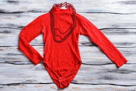 Red bodysuit top and necklace. Girl's top with bead necklace. Bright-colored garment on shelf. New item in stock.