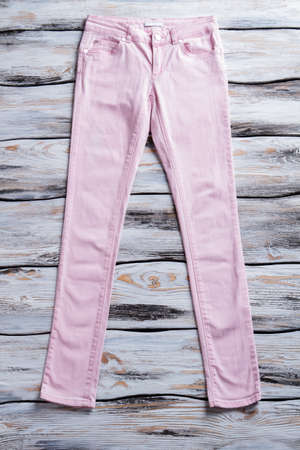 womans clothing: Womans light pink pants. Casual light-colored trousers. Pants laying on white table. Quality piece of clothing.