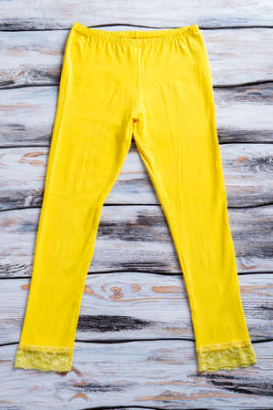 elastic garments: Casual yellow pants. Yellow trousers on wooden background. White shelf with colorful garment. Color of the Sun.