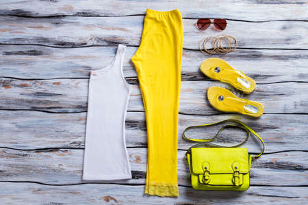 folded clothes: White tank top and pants. Yellow trousers with bracelet set. Folded clothes on wooden table. Womans casual summer outfit.