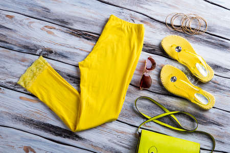 woman's clothing: Bright yellow pants and footwear. Bracelet set with lime bag. Womans clothing on wooden table. New items in stock.