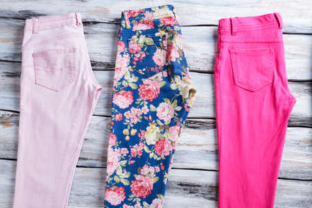 garments: Light pink and floral pants. Girls trousers on wooden background. Colorful summer garments. Quality cotton and stylish print.