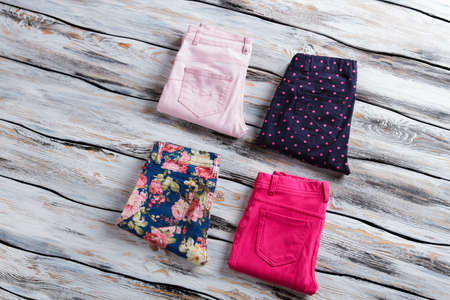 merchandise: Blue and bright pink pants. Womans folded casual trousers. Top quality merchandise on showcase. Clothing from fashion catalog. Stock Photo