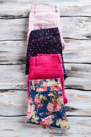discounted: Girls trousers with different pattern. Stylish pants of bright color. Discounted merchandise on showcase. Seasonal discount in boutique.