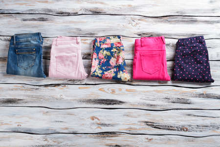womans clothing: Womans bright pants and jeans. Navy trousers and blue jeans. Top quality clothing on display. Dont lose sense of style. Stock Photo