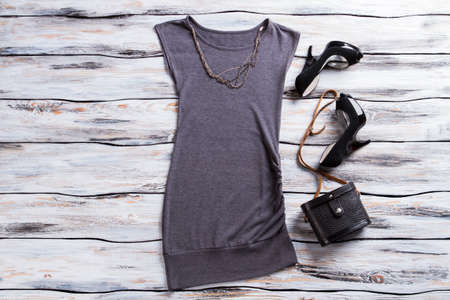 heel strap: Gray sleeveless top and heels. Classic purse with chain necklace. Ladys outfit with luxury shoes. Dark and stylish apparel.