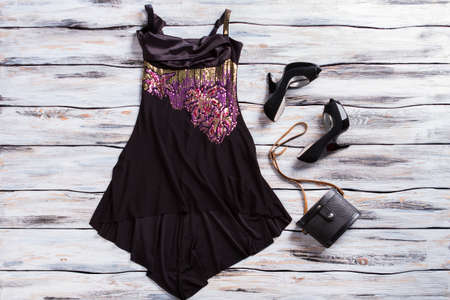 purple shoes: Black sleeveless dress and shoes. Evening dress with purple insert. Luxury female apparel on display. Genuine designer clothes.