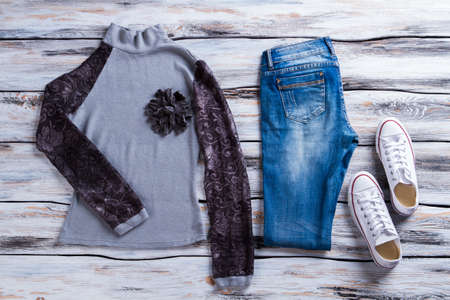 applique flower: Gray top with black sleeves. Sweatshirt, jeans and white shoes. Casual garment with flower applique. New collection of stylish clothes. Stock Photo