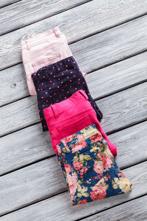 informal clothing: Light pink and navy pants. Folded trousers with stylish print. New goods on gray shelf. Presents for regular customers.