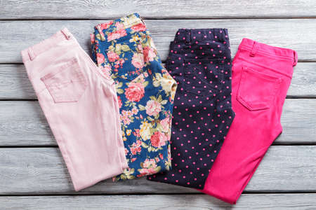 informal clothing: Colorful female pants. Bright and dark folded trousers. Last items on shop showcase. What to wear this spring. Stock Photo