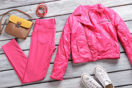 low prices: Bright pink jacket and pants. Brown bag and white shoes. Girls leather bracelets on showcase. Extremely low prices for clothing.