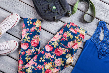 woman's clothing: Floral trousers and blue top. Denim bag and canvas shoes. Womans clothing on gray shelf. Sense of style.