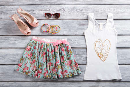 open toe: White tank top and skirt. Floral skirt and salmon shoes. Open toe shoes on display. Clothes from internet shop. Stock Photo