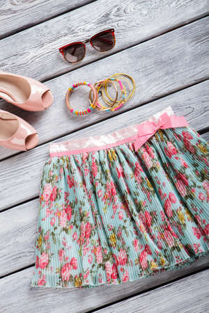 table skirt: Floral skirt and bracelet set. Dark sunglasses and footwear. New merchandise on gray table. Dont miss the sale. Stock Photo