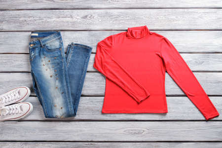 sleeve: Blue jeans and red top. Long sleeve top and shoes. Outfit with white rubber shoes. Ladys casual spring look.